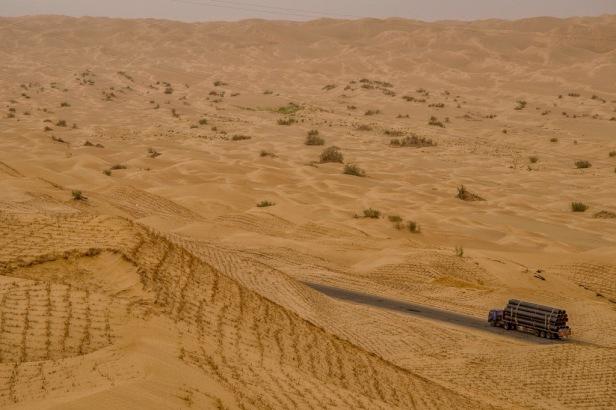 Camión transportando material a través de la Autopista del Taklamakan para los pozos petrolíferos de la zona